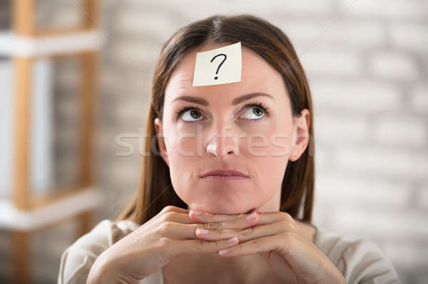 Businesswoman's Forehead With Question Mark On Sticky Note Stock photo © AndreyPopov