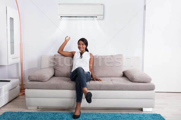 Woman Using Air Conditioner At Home Stock photo © AndreyPopov
