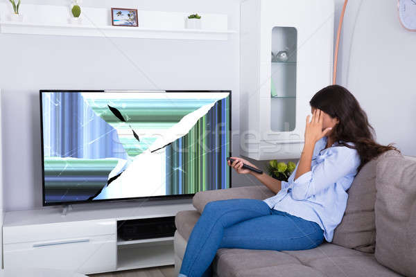 Woman Sitting On Sofa With Broken Television Stock photo © AndreyPopov