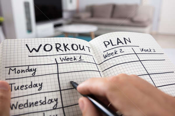 Person Writing Workout Plan In Notebook Stock photo © AndreyPopov