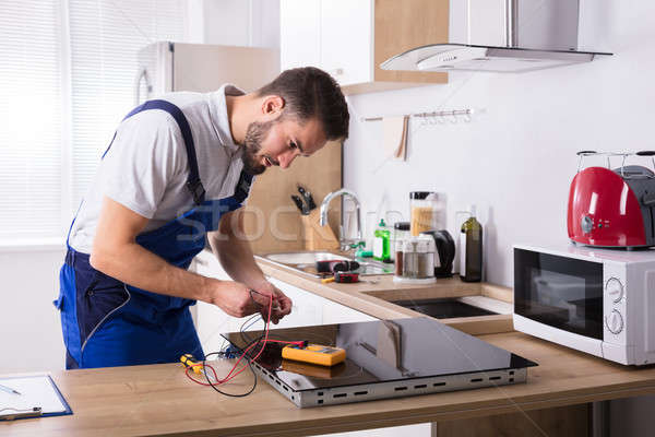 Technician Repairing Induction Stove In Kitchen Stock photo © AndreyPopov