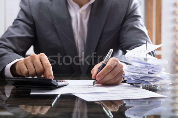 Businessperson's Hand Calculating Invoice Stock photo © AndreyPopov