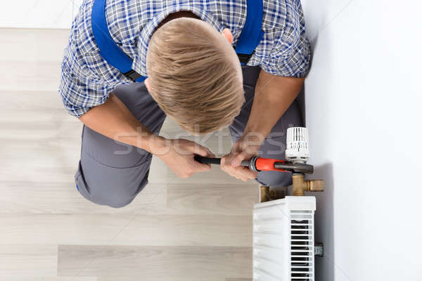 Male Plumber Fixing Thermostat Using Wrench Stock photo © AndreyPopov