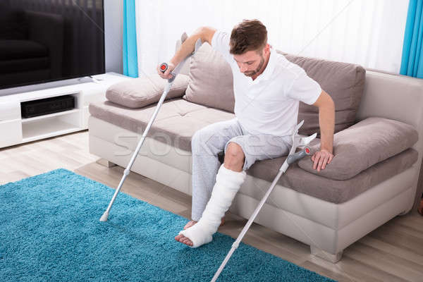 Man With Broken Leg Getting Up From Sofa Stock photo © AndreyPopov