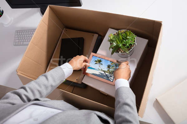 Businesswoman Packing Picture Frame In Cardboard Box Stock photo © AndreyPopov