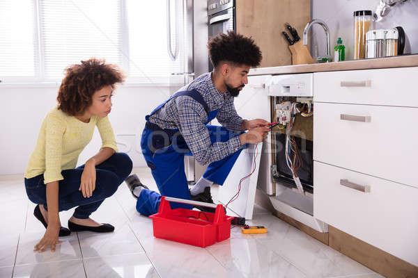 Técnico lavavajillas digital mujer mirando masculina Foto stock © AndreyPopov