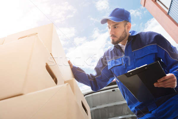 Male Worker Standing Near Cardboard Box Holding Clipboard Stock photo © AndreyPopov