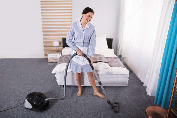 Housekeeper Cleaning Carpet With Vacuum Cleaner Stock photo © AndreyPopov
