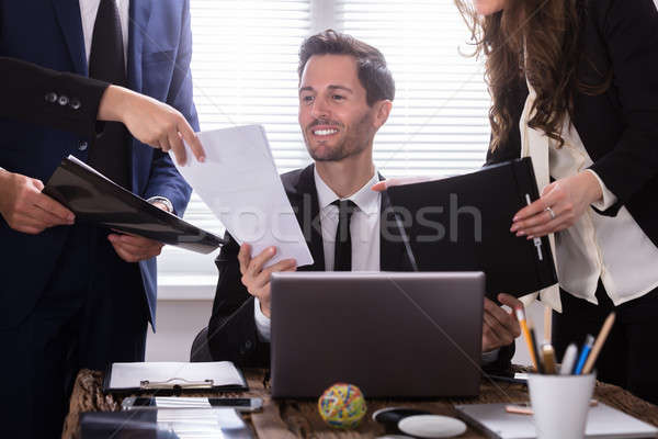 Young Businessman Looking At Document Stock photo © AndreyPopov