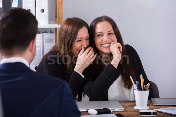 Two Businesswoman Gossiping About Male Colleague Stock photo © AndreyPopov