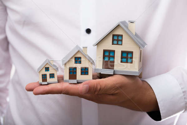 Businessman holding increasing size of house models Stock photo © AndreyPopov