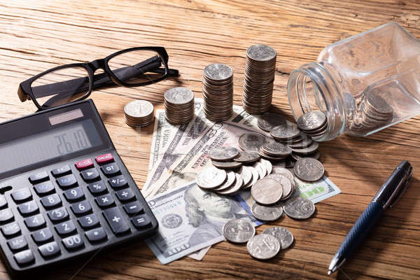 Currency And Calculator With Pen On Wooden Table Stock photo © AndreyPopov
