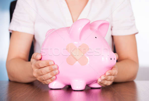Young Businesswoman Holding Piggybank With Band Aid Stock photo © AndreyPopov