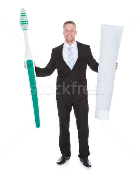 Smiling business man holding a large outsized toothbrush Stock photo © AndreyPopov