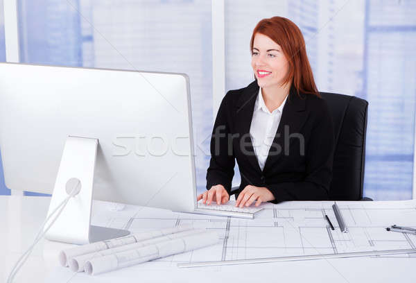 Businesswoman Using Computer With Blueprints At Desk Stock photo © AndreyPopov