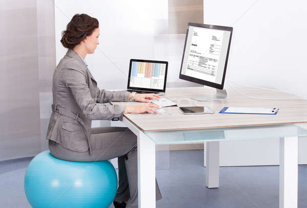 Woman Sitting On Pilates Ball Using Computer Stock photo © AndreyPopov