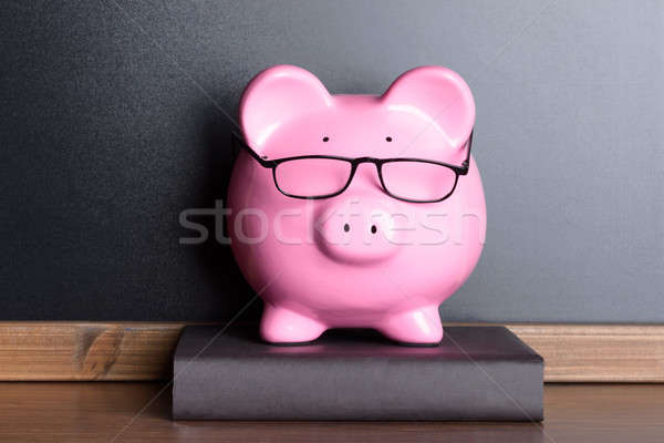 Piggy Bank With Eye Glasses On Book Stock photo © AndreyPopov