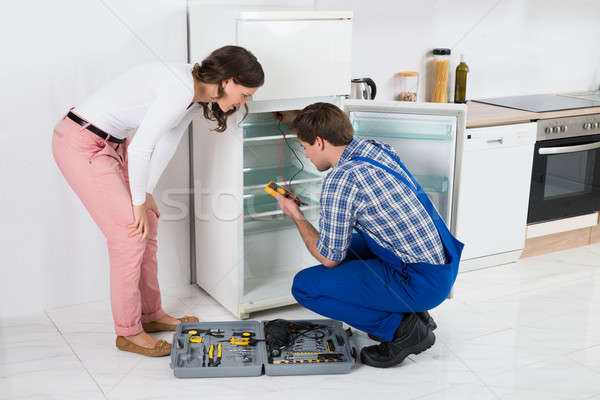 Housewife Looking At Worker Repairing Refrigerator Stock photo © AndreyPopov