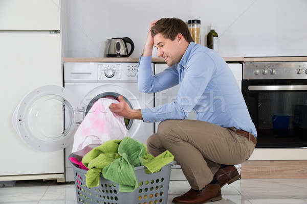 Man With Laundry Basket Holding Stained Cloth Stock photo © AndreyPopov