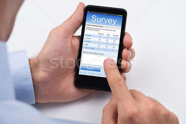 Személy tömés felmérés űrlap mobiltelefon közelkép Stock fotó © AndreyPopov