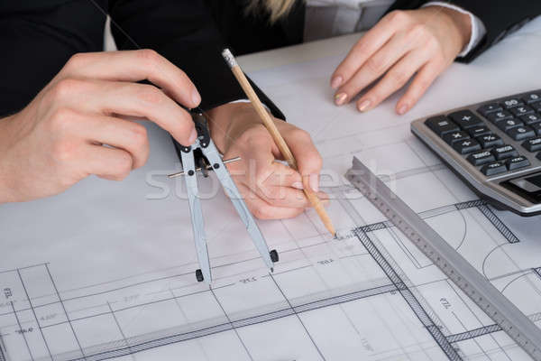 Architects Working On Blueprint At Desk In Office Stock photo © AndreyPopov