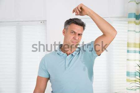 Man Suffering From Backache While Standing Against Wall Stock photo © AndreyPopov