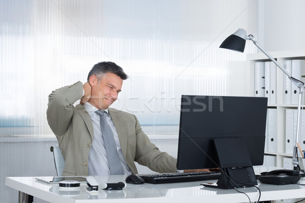 Empresario sufrimiento dolor de cuello escritorio maduro oficina Foto stock © AndreyPopov