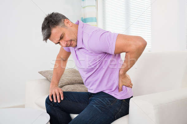 Man Having Backache While Sitting On Sofa Stock photo © AndreyPopov
