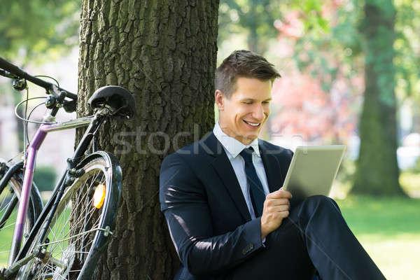 Businessman Using Digital Tablet In Park Stock photo © AndreyPopov