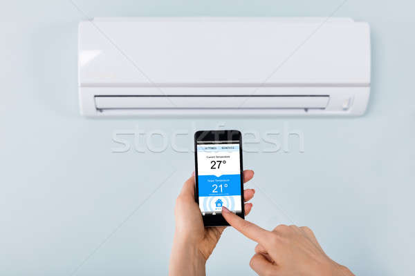 Person Hand Holding Mobilephone Near Air Conditioner Stock photo © AndreyPopov