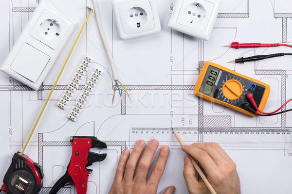 Architect Drawing Plan On Blueprint With Electrical Components Stock photo © AndreyPopov