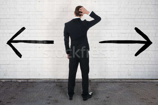 Confused Businessman Looking At Opposite Arrow Signs On Wall Stock photo © AndreyPopov