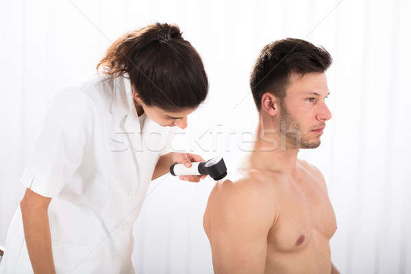 Doctor Examining Skin Of Male Patient With Dermatoscope Stock photo © AndreyPopov