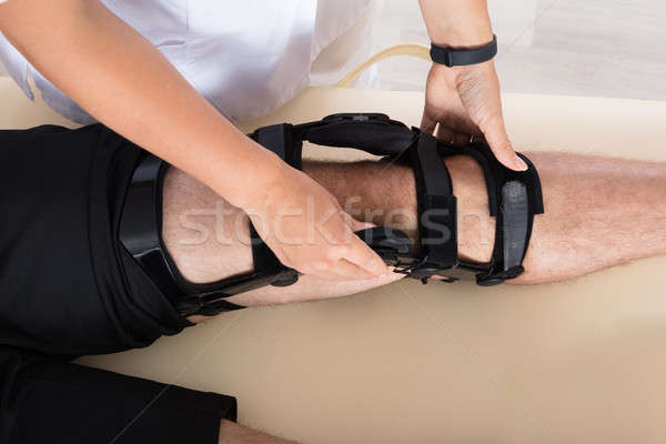 Physiotherapist Fixing Knee Braces On Man's Leg Stock photo © AndreyPopov