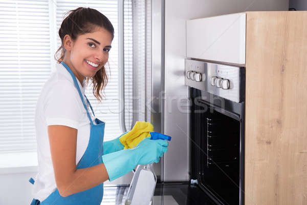 Woman In Protective Gloves Cleaning Oven Stock photo © AndreyPopov