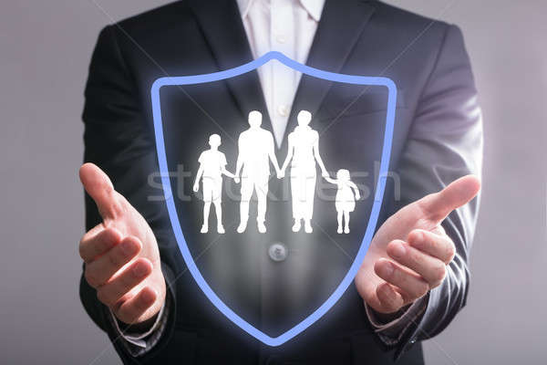 Businessperson's Hand With Shield Protecting Family Stock photo © AndreyPopov