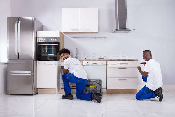 Two Handy Men Fixing The Wooden Cabinet In The Kitchen Stock photo © AndreyPopov
