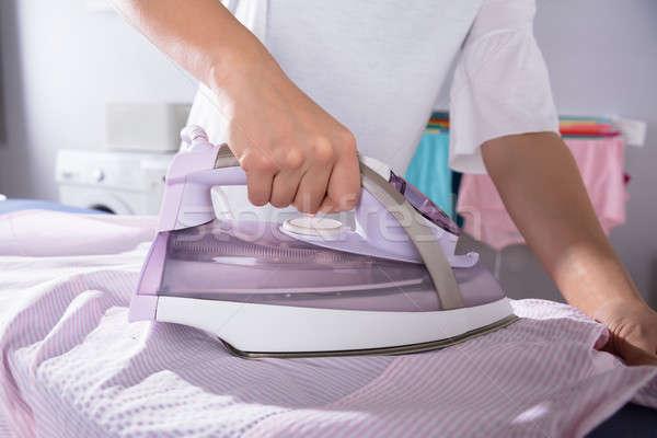 Woman Ironing Cloth On Ironing Board Stock photo © AndreyPopov