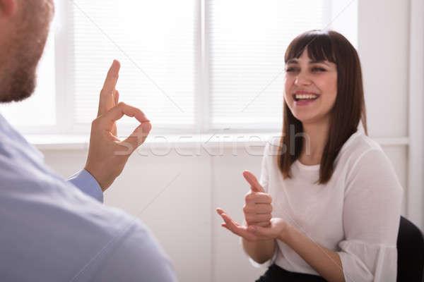 Mulher jovem homem falante linguagem gestual sorridente branco Foto stock © AndreyPopov