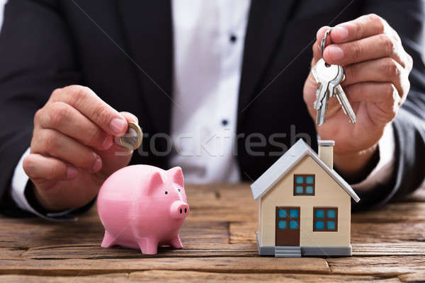Businessperson holding coin and key over piggybank and house Stock photo © AndreyPopov