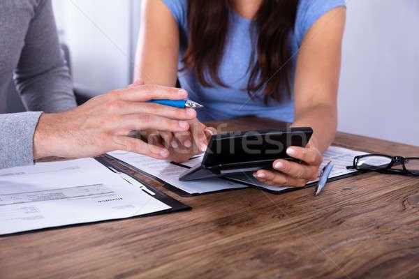 Couple Calculating Invoice With Calculator Stock photo © AndreyPopov