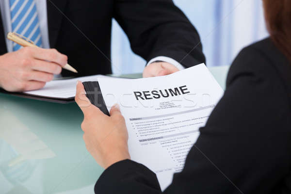 Female Candidate Holding Resume At Desk Stock photo © AndreyPopov