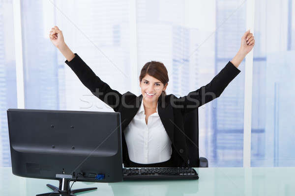 Businesswoman With Arms Raised At Computer Desk Stock photo © AndreyPopov