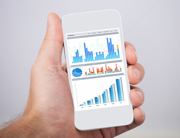 Hand Holding Mobile Phone With Financial Charts Stock photo © AndreyPopov