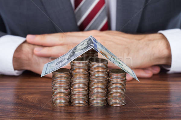 Empresário moedas casa secretária homem Foto stock © AndreyPopov