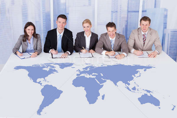 Business People Sitting At Conference Table With World Map Stock photo © AndreyPopov