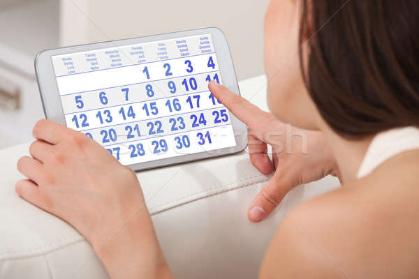 Woman Using Calendar On Digital Tablet At Home Stock photo © AndreyPopov