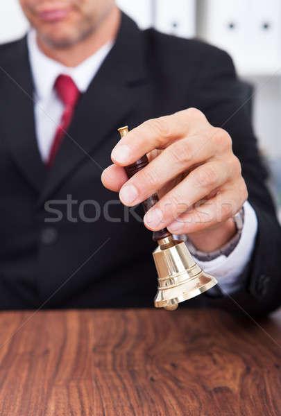 бизнесмен колокола стороны деревянный стол Сток-фото © AndreyPopov