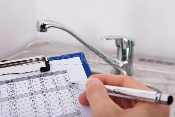 Stock photo: Hand Writing Consumption Level On Clipboard