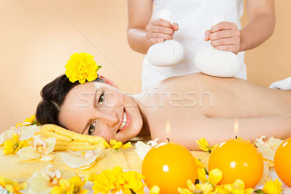 Woman Receiving Massage With Herbal Compress Stamps At Spa Stock photo © AndreyPopov